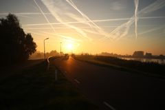 Sunrise with colored aircraft trails, fog on the meadows and at River Hollandsche IJssel. In the Netherlands at nieuwerkerk stock photos