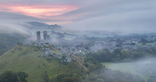 Sunrise at Corfe castle in mist Stock Photo