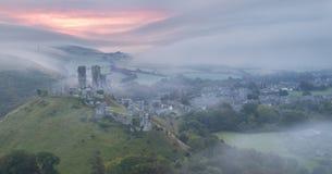 Sunrise at Corfe castle in mist Stock Photo
