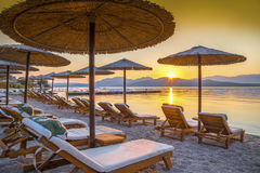 Sunrise, Corfu, Greece. Beautiful sunrise over the beach in Corfu island, with chairs and umbrellas near the sea, in Greece Royalty Free Stock Photos