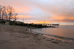 Sunrise at Crescent Beach. Beach and pier highlighted by colours of sunrise in clouds and on the water stock photography