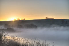 Sunrise cresting hilltop. The sun is cresting a hilltop before a lake covered in mist Stock Photography