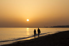 Sunrise in Crete. A couple walking together on the beach in Crete Royalty Free Stock Images