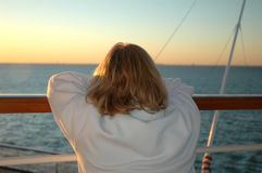 Sunrise Cruise Lady. A lady watches the sun rise from the deck of a cruise ship Royalty Free Stock Images