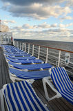 Sunrise on cruise ship deck. Sunrise on deck of a cruise ship with striped white and blue deck chairs stock photography