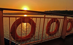 Sunrise on the Dardanelles, Turkey. And fence with lifejackets of the ship Stock Image