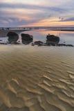 Sunrise dawn landscape on rocky sandy beach with vibrant sky and Stock Photo