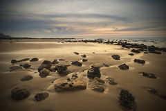 Sunrise dawn landscape on rocky sandy beach with vibrant sky and Royalty Free Stock Photo