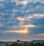 Sunrise dramatic clouds city. The sun`s rays make their way through the dark dramatic clouds over the city of Ivano-Frankivsk, Ukraine Stock Photo