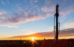 Sunrise Drill. Construction large drill standing tall with a sunrise sky Stock Photo