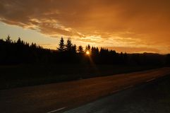 Sunrise. Driving at 3 ó clock in the morning in the North of Norway and the sun painting everything in gold Royalty Free Stock Photo