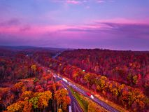 Sunrise from a drone with cloudy skies. Yellow sunrise over the horizon and mountains and traffic  going by with trees in autumn Stock Photography