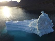 Sunrise drone image of a large grounded iceberg near a rocky shoreline in western Greenland. Drone image taken during a sailing expedition to western Greenland stock photography