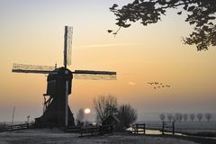 Sunrise on the Dutch windmill. Ducks fying over a beautiful early morning and warm Kinderdijk sunrise on windmills and a canal bridge nearby Alblasserdam and Stock Photography