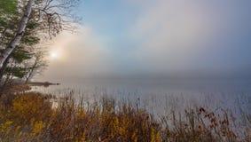 Sunrise through early morning fog on a lake near Ottawa, Ontario. Stock Photos