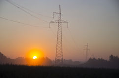 Sunrise and electric power stations on field Royalty Free Stock Photography