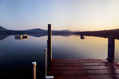 Sunrise at the end of the dock. Early morning Summer sunlight creeps over a dock on a New Hampshire lake royalty free stock photo