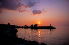 Sunrise At The Entrance To The Marina. The sun rises over the breakwater and protected entrance to the yacht club on Lake Ontario in Port Credit, Ontario stock image