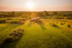 Sunrise on the Farm. Chickens clucking and roosters crowing as the morning sun warms the farmyard, flower and vegetable gardens and a chicken coop Royalty Free Stock Image