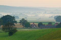 Sunrise farmland. Sunrise over a misty farm in the hills Royalty Free Stock Images