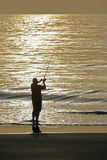 Sunrise Fisherman. A sunrise surf fisherman gets a bite Royalty Free Stock Image