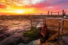 Sunrise and fisherman at Mona Vale Australia. Sunrise and fisherman silhouetted at Mona Vale rock shelf viewed from the edge of the famous rock pool, a crab royalty free stock photo