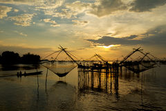 Sunrise at the fisherman village with silhouette of wooden fishing net and long tail wooden boat Royalty Free Stock Photos