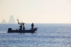 Sunrise with fishermen at sea stock photos