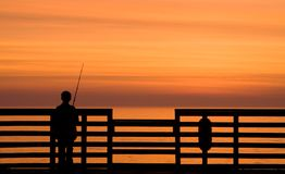 Sunrise Fishing. Boy fishing off a pier during sunrise Royalty Free Stock Images