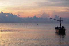 Sunrise with a fishing boat stock images