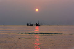 Sunrise with fishing boat Stock Image