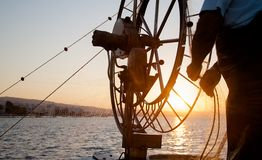Sunrise on a fishing boat with a net in the sea. Hands of old fisherman Royalty Free Stock Photography