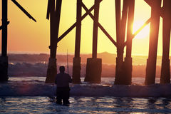 Sunrise fishing by the pier Royalty Free Stock Photography