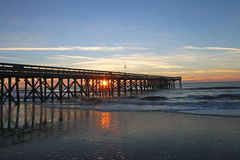 Sunrise through fishing pier at Isle of Palms SC Royalty Free Stock Images