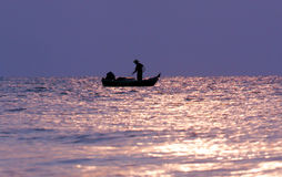 Sunrise at fishing village. Fisherman casts net during sunrise royalty free stock photo