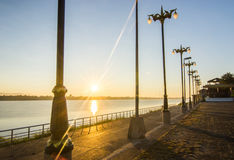 Sunrise flare in the river with light poles Royalty Free Stock Images