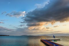 Sunrise with fluffy clouds on a golden blue sky over calm sea wi Stock Photos