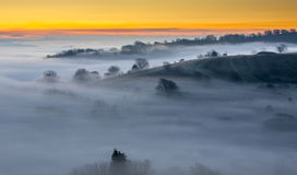 Sunrise fog. Lanscape view showing successive line of tree-topped hills emerging from a thick layer of radiation fog Royalty Free Stock Photo