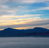 The sunrise, fog and mountain peaks. Royalty Free Stock Image