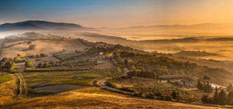 Sunrise with Fog over Tuscan village Stock Photos