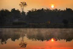 Sunrise in fog and reflection Royalty Free Stock Photography