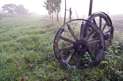 Sunrise on foggy autumn landscape with two antique wooden wheels Stock Image