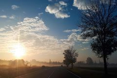 Sunrise on a foggy morning. The sun rises above the horizon and illuminates the road royalty free stock images