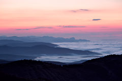 Sunrise at foggy mountain valley Stock Images