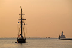 Sunrise, frigate and a lighthouse. Sunrise and leaving frigate near a lighthouse Stock Images