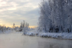 Sunrise on the frosty river. Frozen river flanked by white frost trees in the bright winter sun, after a chilling and foggy night Stock Photos