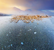 Sunrise on the frozen lake in winter mountains Royalty Free Stock Photo