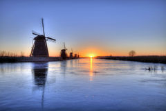 Sunrise on the frozen windmills alignment Royalty Free Stock Photography