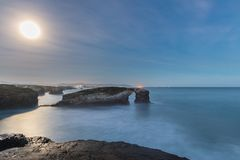 Sunrise with full moon on the beach of the cathedrals. Where the moonlight is reflected in the sea Stock Images
