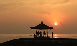 Sunrise at gazebo Bali, Indonesia. People enjoying early morning breeze at the gazebo. Low tide Stock Image